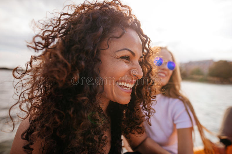 Cheerful young woman outdoors with female friend stock photos