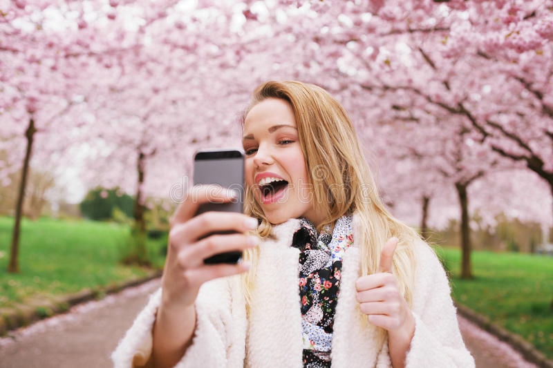 Cheerful young woman photographing herself at spring park. Cheerful young woman talking her picture with her cell phone and gesturing thumbs up sign. Caucasian royalty free stock images