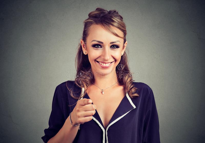 Cheerful young woman pointing finger at camera royalty free stock images
