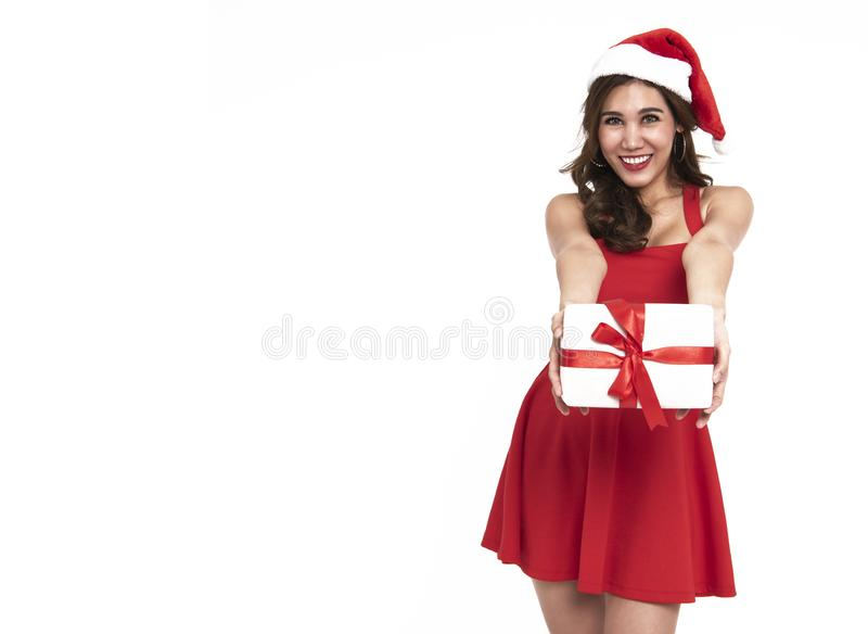 Cheerful young woman in red dress santa holding gift box for christmas isolated on white background. royalty free stock photos