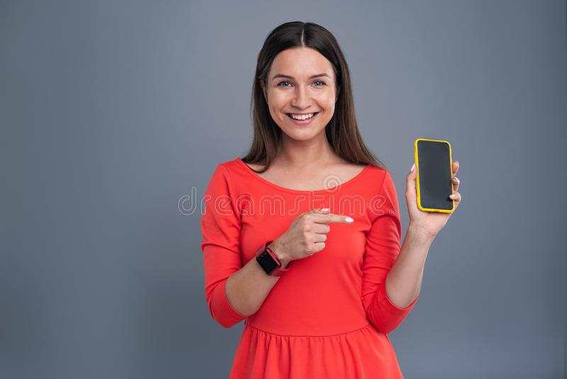 Cheerful young woman in red dress showing her phone stock photos
