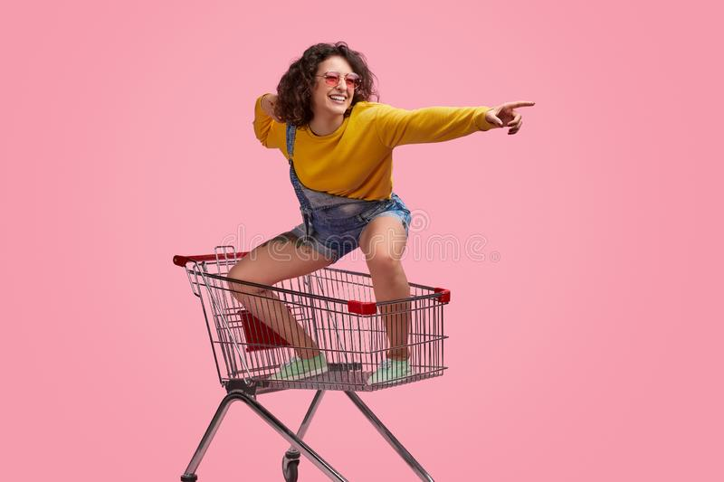 Cheerful young woman riding forward on shopping cart royalty free stock photos