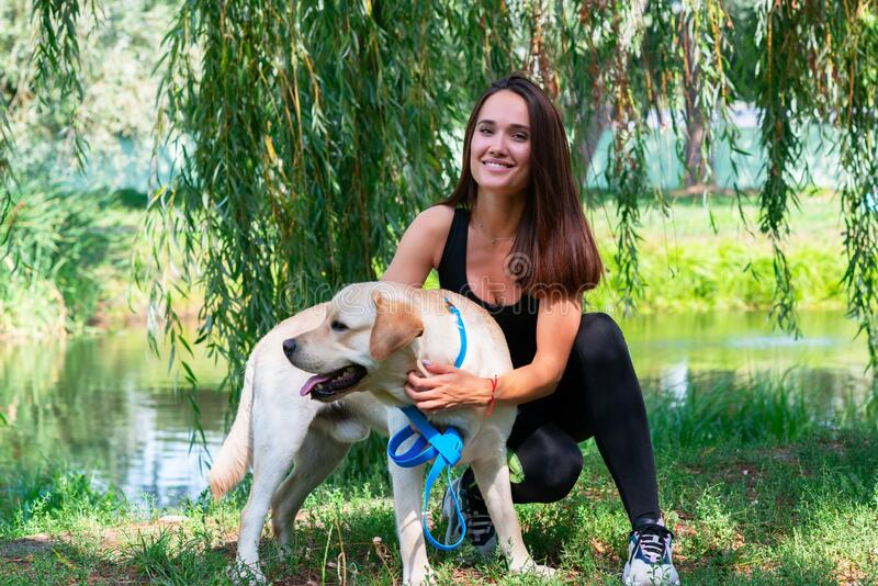 Cheerful young woman sitting and hugging her dog at river bank in summer park. Cheerful pretty young woman sitting and hugging her dog at river bank in summer royalty free stock photos