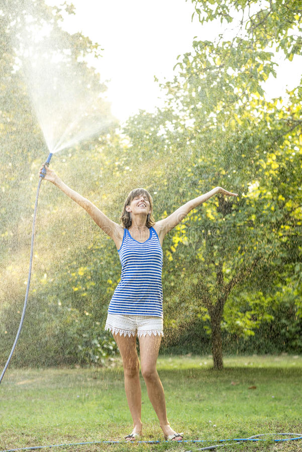 Cheerful young woman spraying herself with water on a hot summer. Day holding the hosepipe above her head as she stands in a beam of warm light from the sun royalty free stock photo