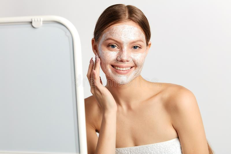 Cheerful young woman standing in front of the the mirror with mask on her face. stock photography