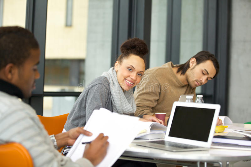 Cheerful young woman studying in the university stock images