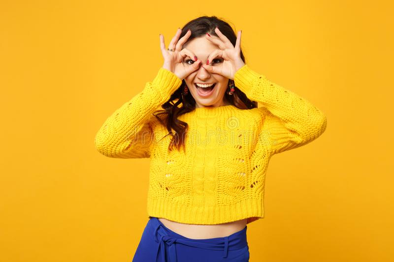 Cheerful young woman in sweater blue trousers hold hands near eyes imitating glasses or binoculars isolated on yellow. Orange background. People sincere stock photos