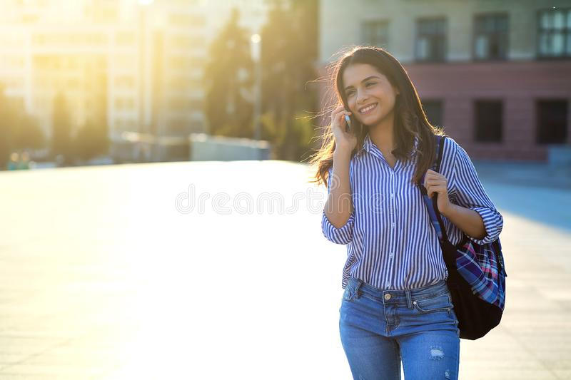 Cheerful young woman talking by phone outdoors with sunlight on her face and copy space stock photos