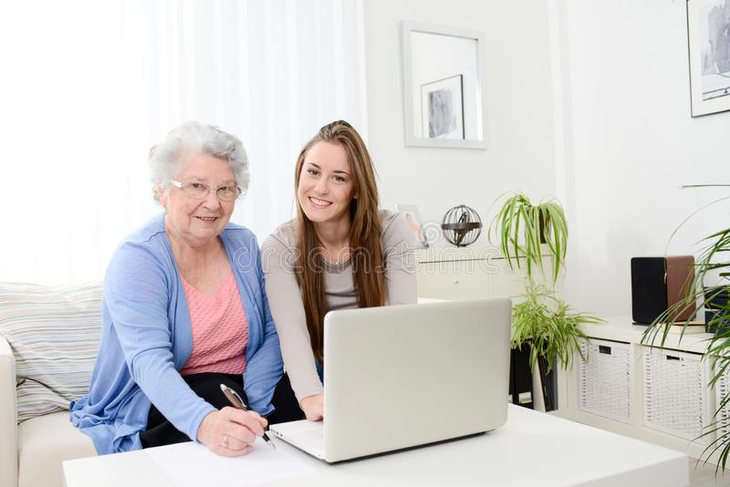 Cheerful young woman teaching computer to an old senior woman at home. Cheerful young women teaching how to use computer to an old senior women at her home royalty free stock image