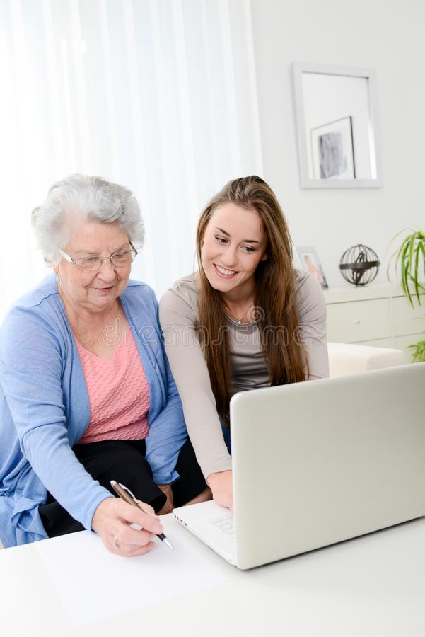 Cheerful young woman teaching computer to an old senior woman at home. Cheerful young women teaching how to use computer to an old senior women at her home royalty free stock photos