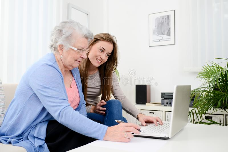 Cheerful young woman teaching computer to an old senior woman at home. Cheerful young women teaching computer to an old senior women at her home stock images