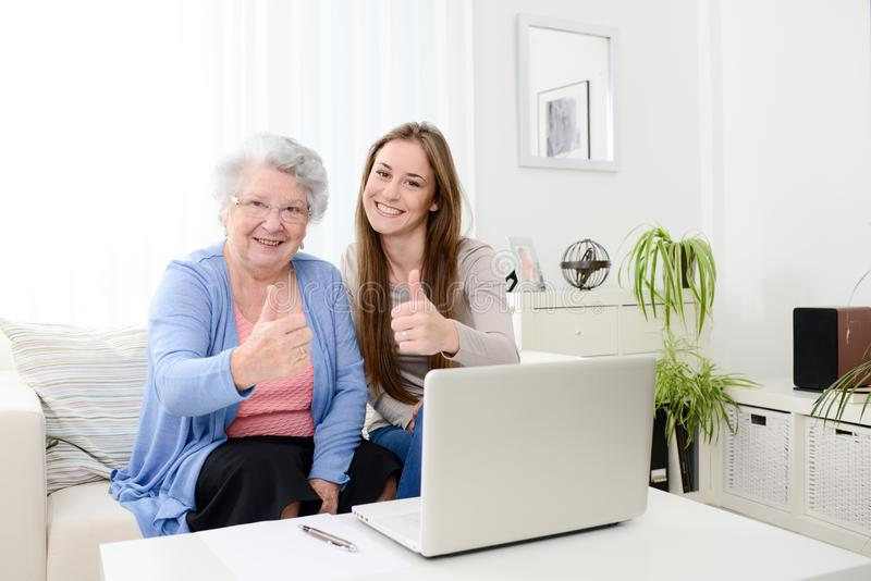 Cheerful young woman teaching computer to an old senior woman at home. Cheerful young women teaching computer to an old senior women at her home royalty free stock image