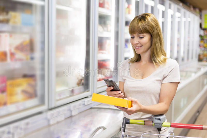 Cheerful young woman texting on mobile phone in supermarket. royalty free stock photos