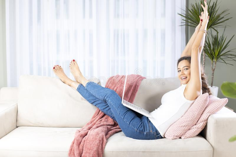 Young woman using laptop on sofa stock image