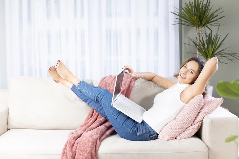 Young woman using laptop on sofa stock photo