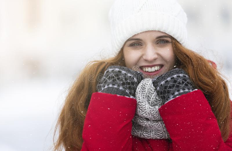 Cheerful young girl in warm clothes enjoying snowy winter day royalty free stock images