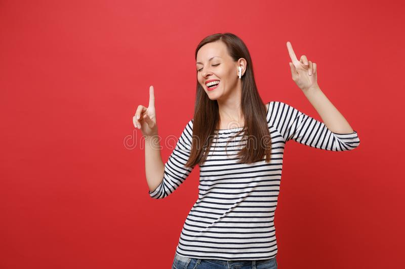 Cheerful young woman with wireless earphones dancing, pointing index fingers up, listening music isolated on bright red stock photo