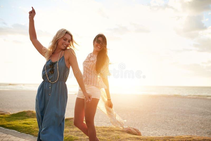 Cheerful young women enjoying and dancing on a beach. stock photo