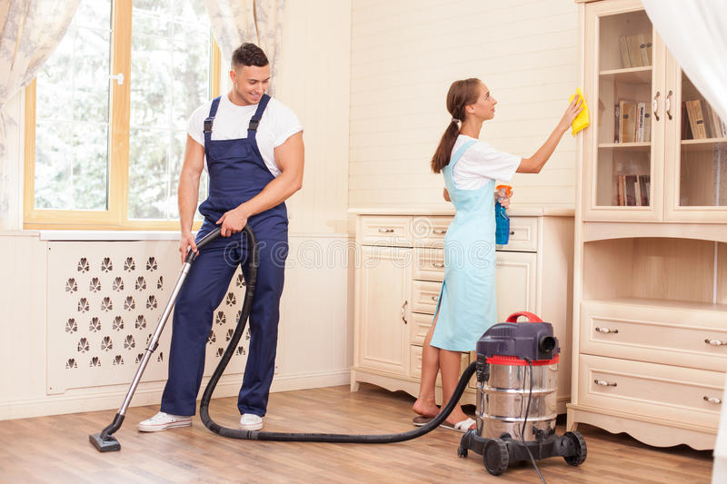 Cheerful young workers are cleaning the house with stock for House cleaning stock photos