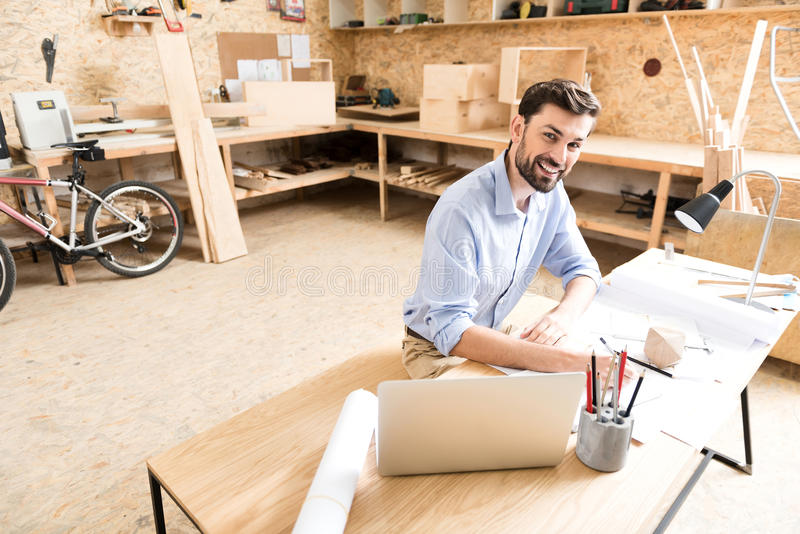 Cheerful youthful timber craftsman making drafts of product in workshop. Waist up portrait of jolly young bearded woodworker sitting at table and drawing royalty free stock image