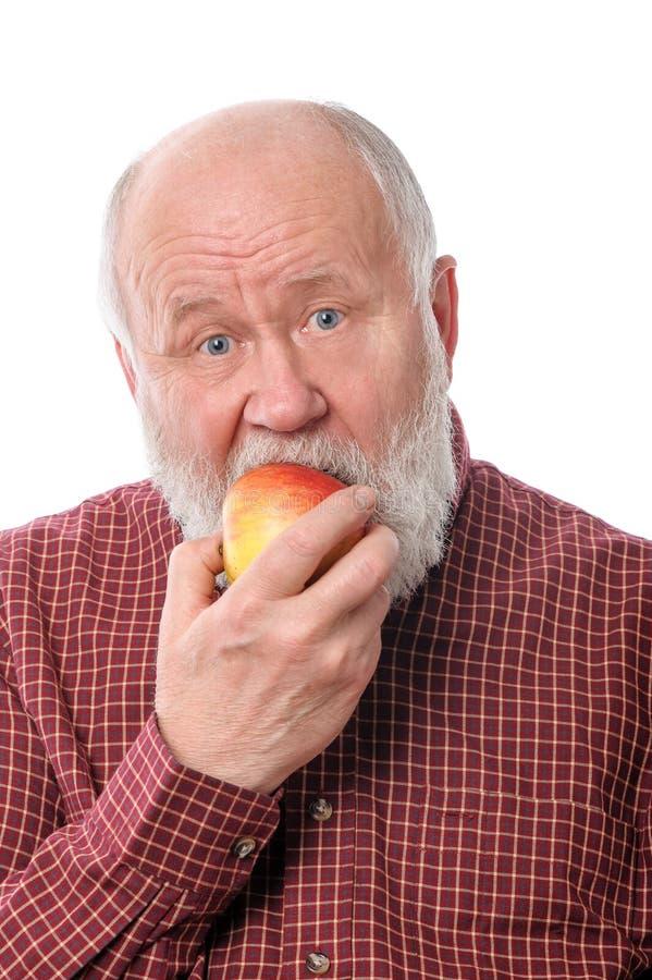 Cheerfull senior man eating the apple, isolated on white royalty free stock photo