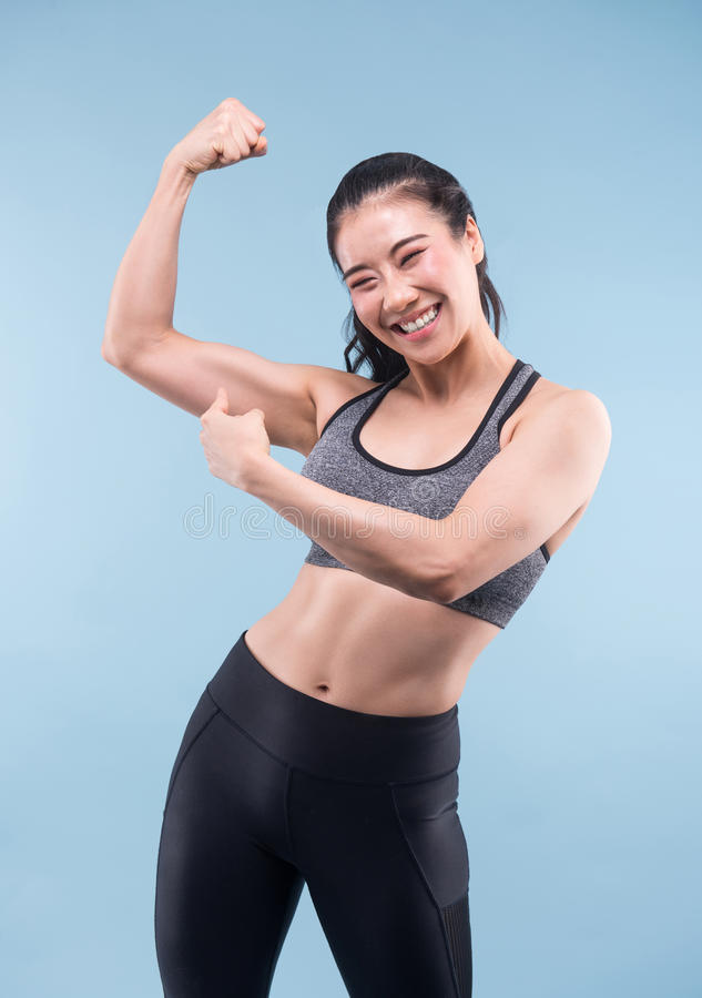 Cheerfully smiling asian sporty woman demonstrating biceps. stock image