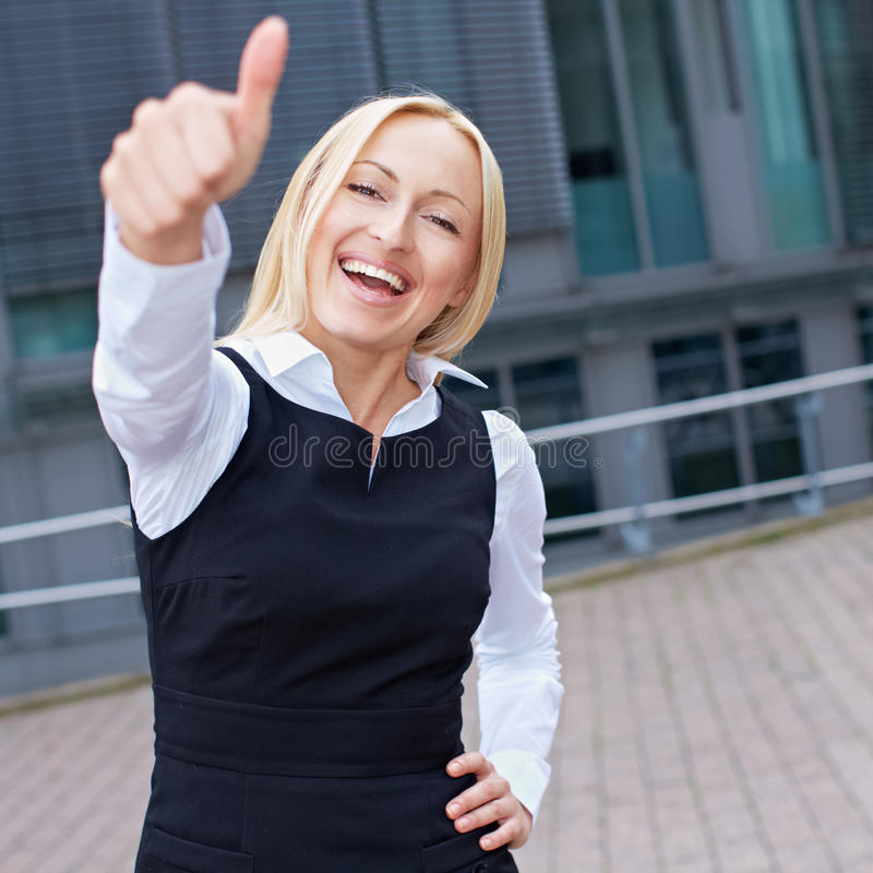 Cheering. Happy business woman holding her thumbs up stock photo