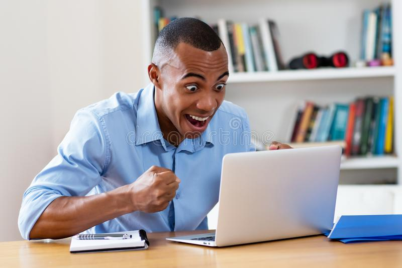 Cheering african american man at computer. At home at office stock image