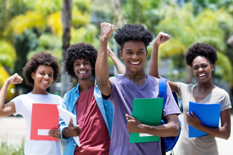 Cheering african male student with group of african american students. Outdoor in the summer stock image
