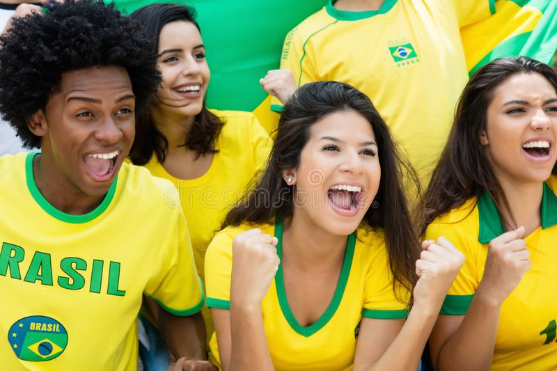 Cheering brazilian soccer fans with flag at stadium. Cheering brazilian soccer fans with jersey an flag at stadium stock photography