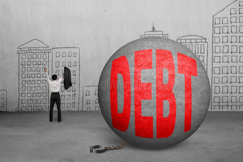 Cheering businessman free from debt ball shackle. With doodles wall royalty free stock photo