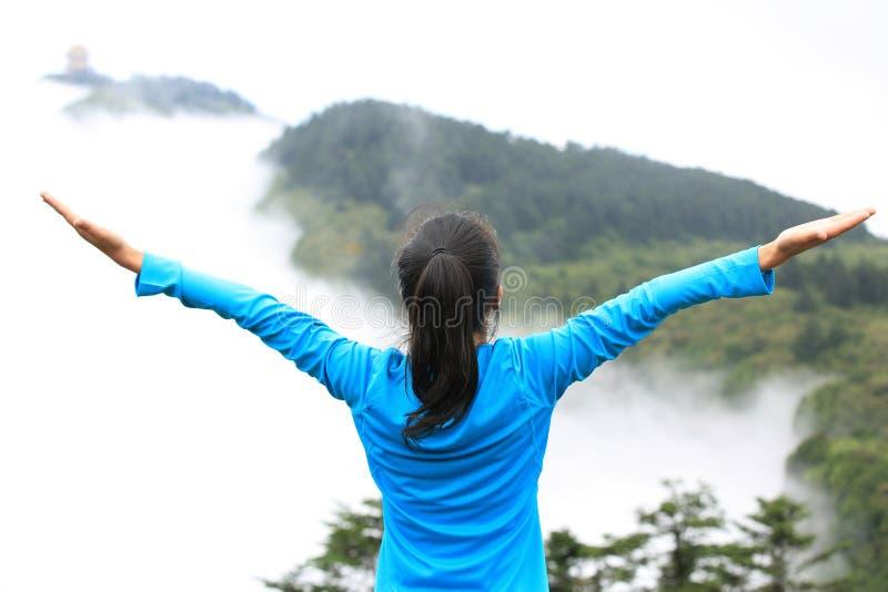 Cheering caminhando a mulher aprecia a vista bonita no pico de montanha imagens de stock