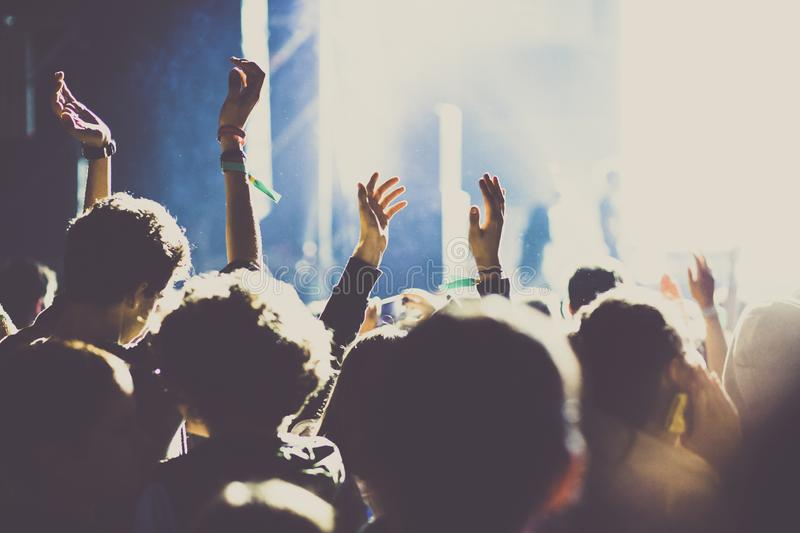 Cheering crowd with raised hands at concert - music festival. Applauding, arms, audience, background, band, celebration, cheerful, club, dance, dancing, disco royalty free stock photography