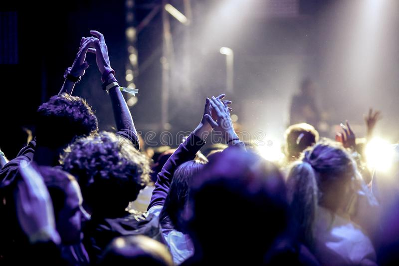 Cheering crowd with raised hands at concert - music festival. Applauding, arms, audience, background, band, celebration, cheerful, club, dance, dancing, disco royalty free stock photo