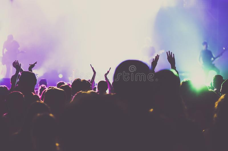 Cheering crowd with raised hands at concert - music festival. Applauding, arms, audience, background, band, celebration, cheerful, club, dance, dancing, disco stock photos