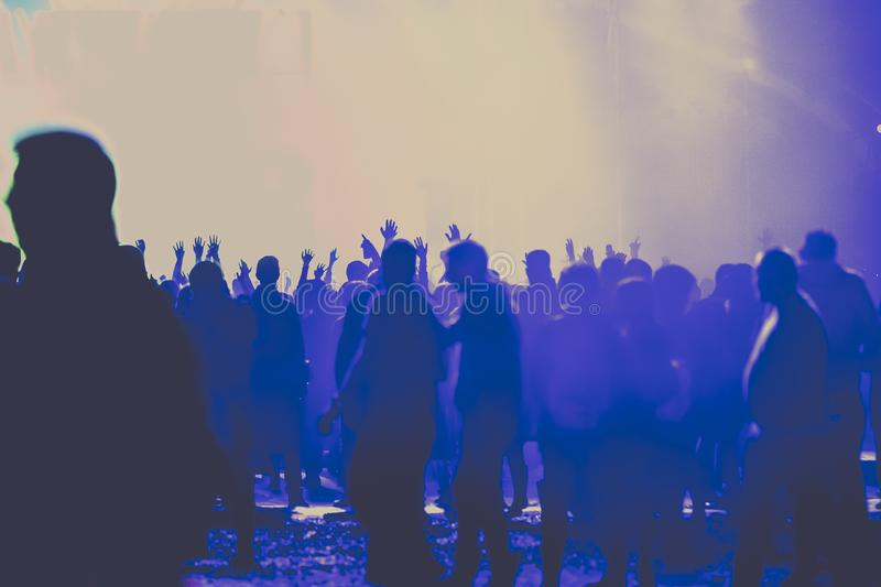 Cheering crowd with raised hands at concert - music festival. Applauding, arms, audience, background, band, celebration, cheerful, club, dance, dancing, disco stock photography