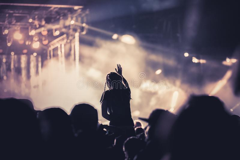 Cheering crowd with raised hands at concert - music festival. Applauding, arms, audience, background, band, celebration, cheerful, club, dance, dancing, disco stock photo