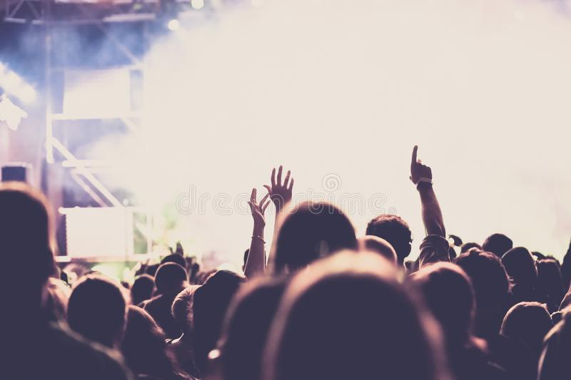 Cheering crowd with raised hands at concert - music festival. Applauding, arms, audience, background, band, celebration, cheerful, club, dance, dancing, disco royalty free stock photos
