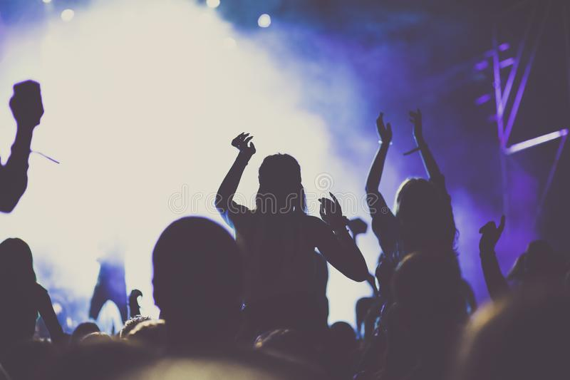 Cheering crowd with raised hands at concert - music festival. Applauding, arms, audience, background, band, celebration, cheerful, club, dance, dancing, disco royalty free stock image