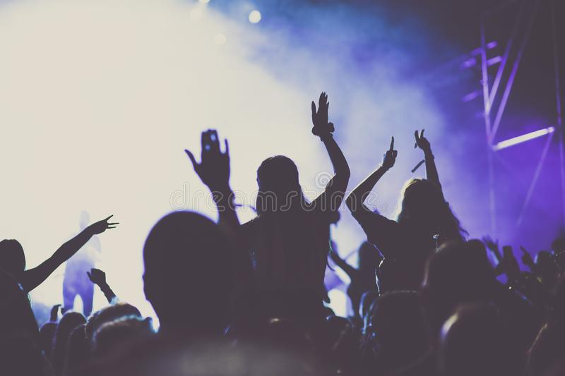Cheering crowd with raised hands at concert - music festival. Applauding, arms, audience, background, band, celebration, cheerful, club, dance, dancing, disco stock images