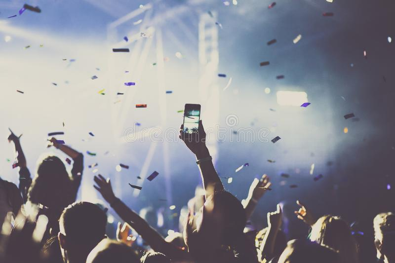 Cheering crowd with raised hands and falling confetti at concert - music festival. Applauding, arms, audience, background, band, celebration, cheerful, club stock photography