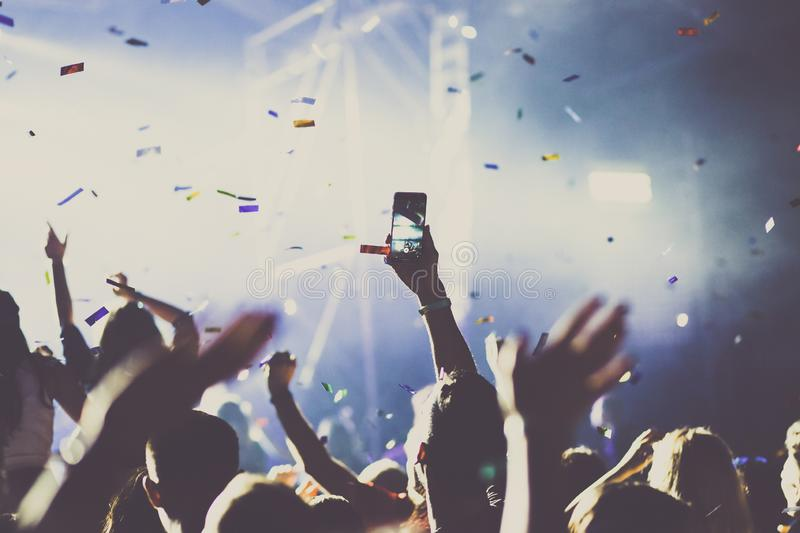 Cheering crowd with raised hands and falling confetti at concert - music festival. Applauding, arms, audience, background, band, celebration, cheerful, club stock photos