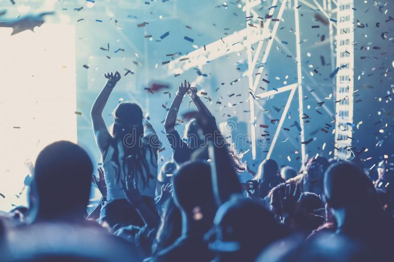 Cheering crowd with raised hands and falling confetti at concert - music festival. Applauding, arms, audience, background, band, celebration, cheerful, club royalty free stock images