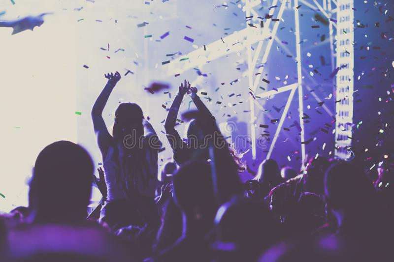 Cheering crowd with raised hands and falling confetti at concert - music festival. Applauding, arms, audience, background, band, celebration, cheerful, club royalty free stock image