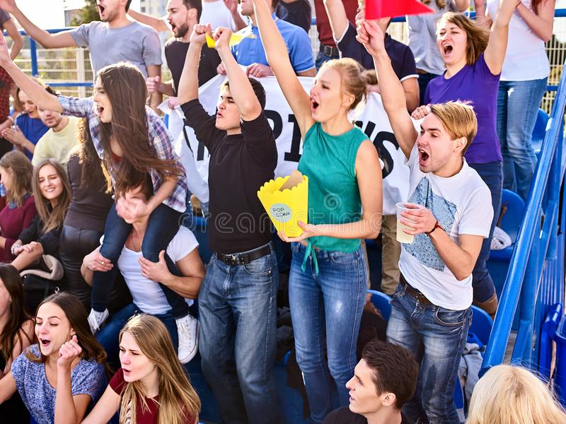 Cheering fans in stadium holding champion banner. Fans cheering in stadium holding champion banner and singing on tribunes. People are waiting for start of royalty free stock photos