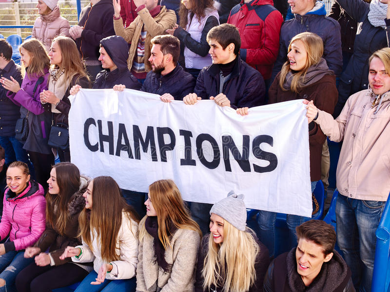 Cheering fans in stadium holding champion banner. Fans cheering in stadium holding champion banner and singing on tribunes. Group young people support your royalty free stock photos