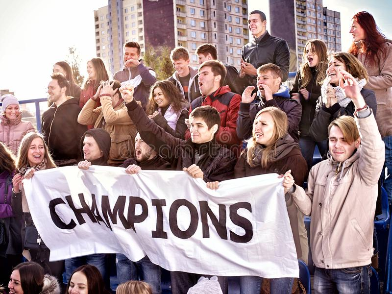 Cheering fans in stadium holding champion banner. Fans cheering in stadium holding champion banner and singing on tribunes. Large group young people together stock images