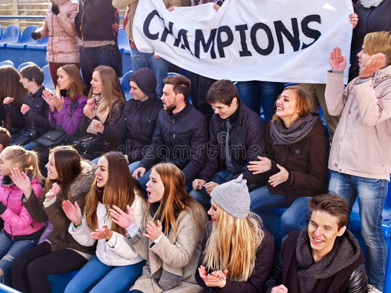 Cheering fans in stadium holding champion banner. Fans cheering in stadium holding champion banner and singing on tribunes. Large group young people together royalty free stock image