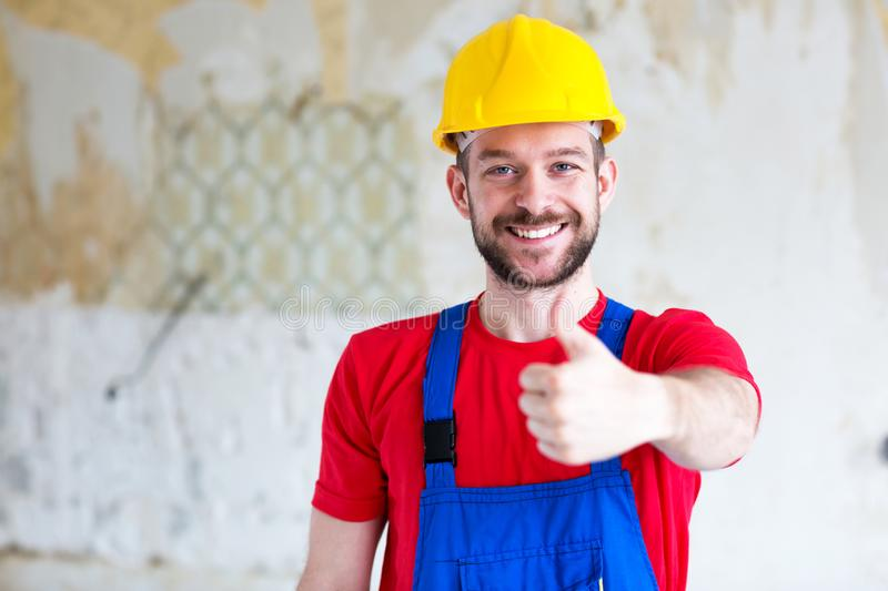Cheering handyman after a job well done. Enjoying in observing details of his work royalty free stock images