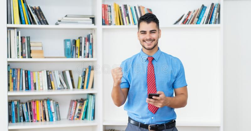 Cheering hispanic hipster zakenman met kopieerruimte en telefoon royalty-vrije stock foto